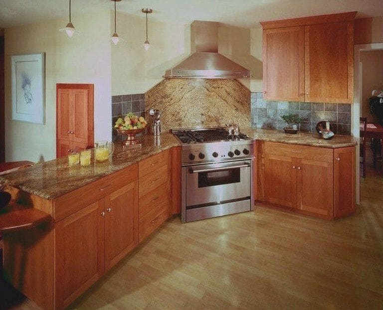 Remodeled Kitchen 4 Growing Family has a professional range and hood at a 45-degree angle, enhanced by Juparana granite in a herringbone pattern.